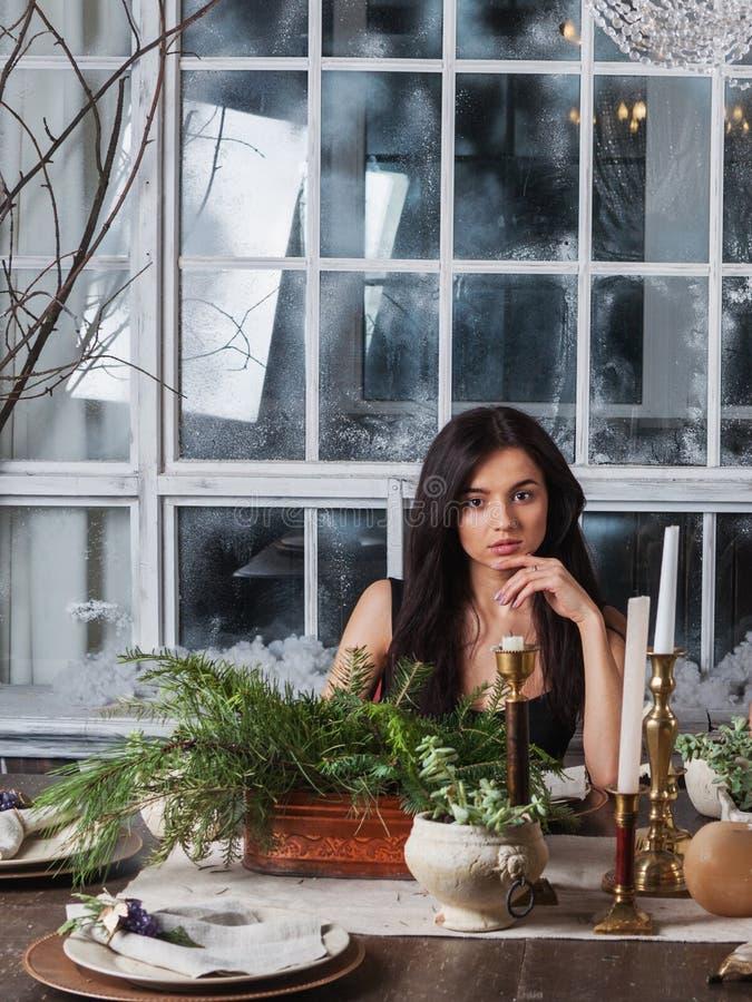 美丽的女孩坐为圣诞节和常青树焦点装饰的餐桌 免版税库存照片