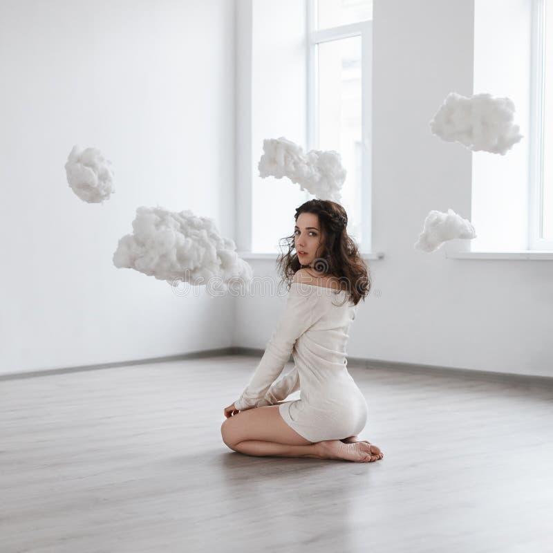 美丽的女孩坐在云彩的地板 库存图片