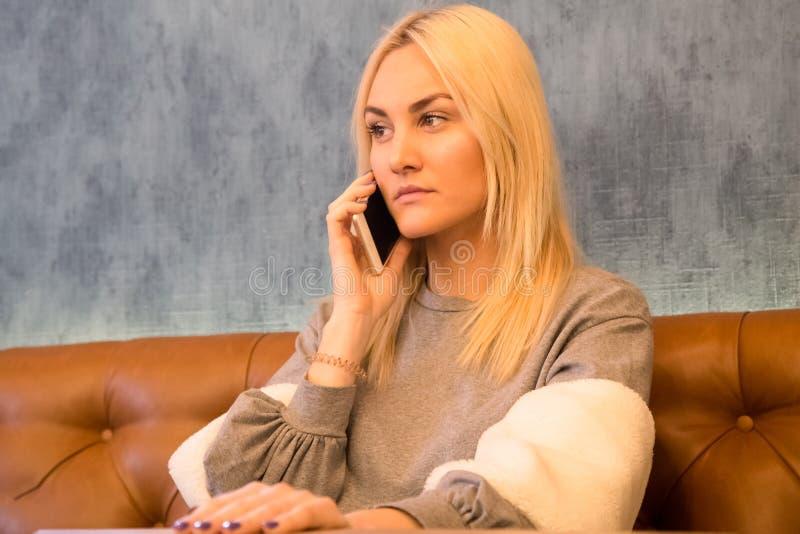 美丽的女孩坐在咖啡馆和谈话在巧妙的电话 免版税库存照片