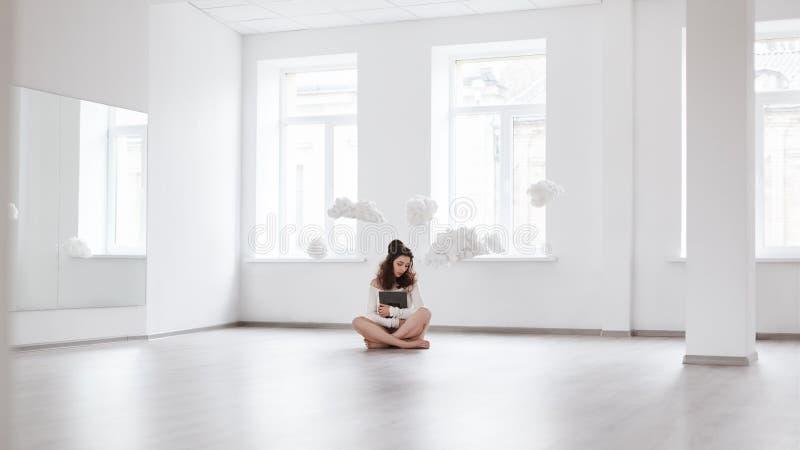美丽的女孩坐在拿着书的云彩的地板 免版税库存图片