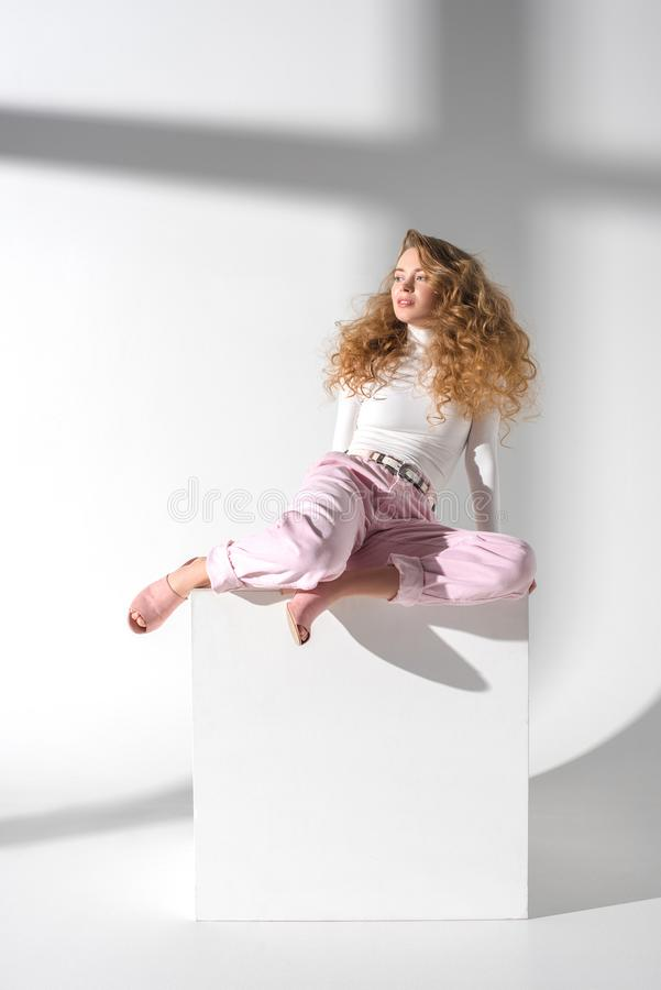 美丽的女孩坐白色立方体 库存照片