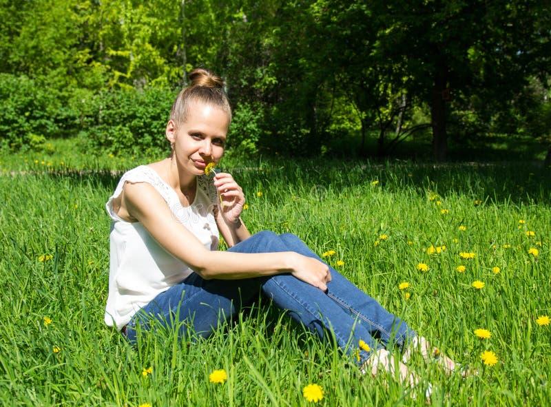 美丽的女孩坐草坪用蒲公英 库存照片