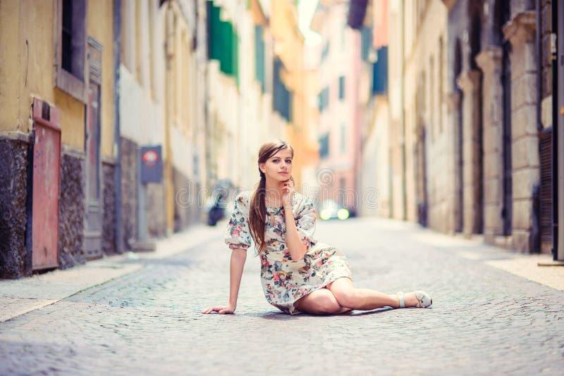 美丽的女孩坐街道 免版税库存图片