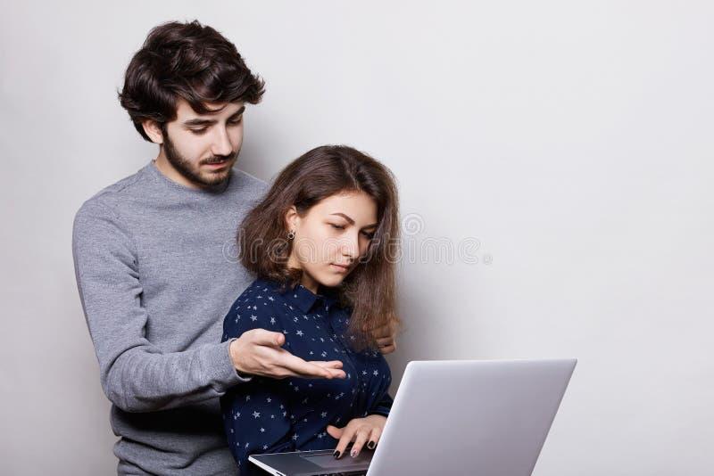 美丽的女孩妇女,享受现代技术,使用她的写的她文凭纸膝上型计算机 一时髦的有胡子的学生tryi 图库摄影