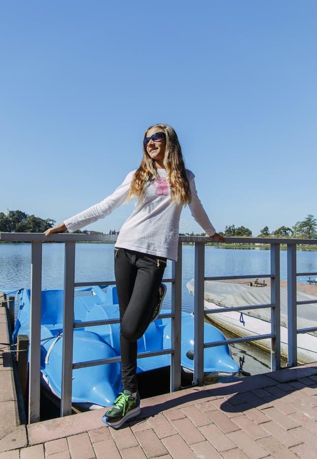 美丽的女孩少年在公园由室外的湖 库存照片