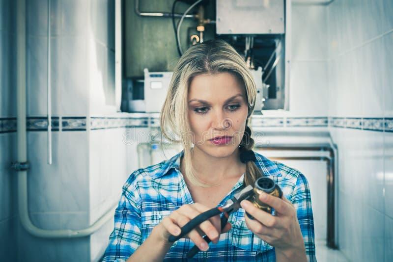 美丽的女孩尝试对Repar一个锅炉 免版税库存照片