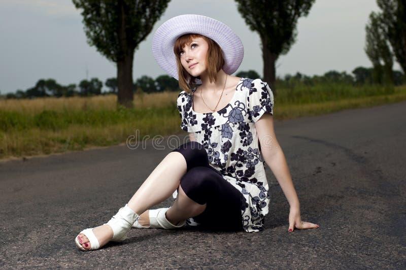 美丽的女孩帽子坐年轻人 免版税库存图片