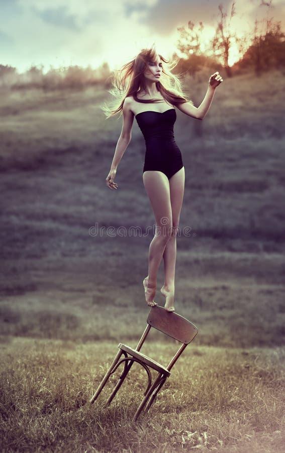 美丽的女孩平衡椅子户外。 免版税库存照片