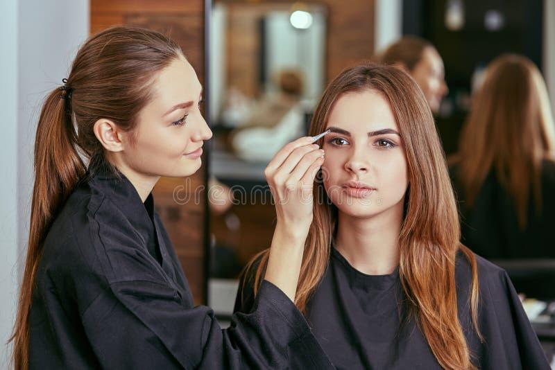 美丽的女孩得到了眼眉的更正在美容院的 库存图片