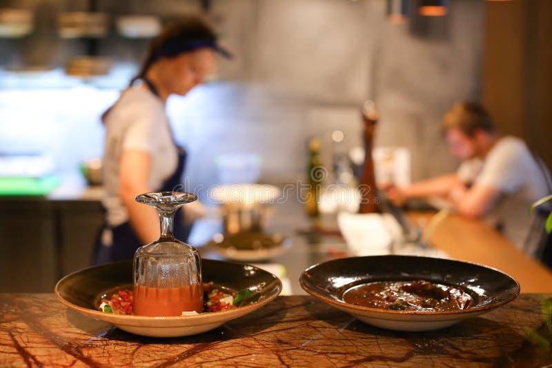 年轻美丽的女孩手厨师倾吐在c的碗现成的饭食 库存图片