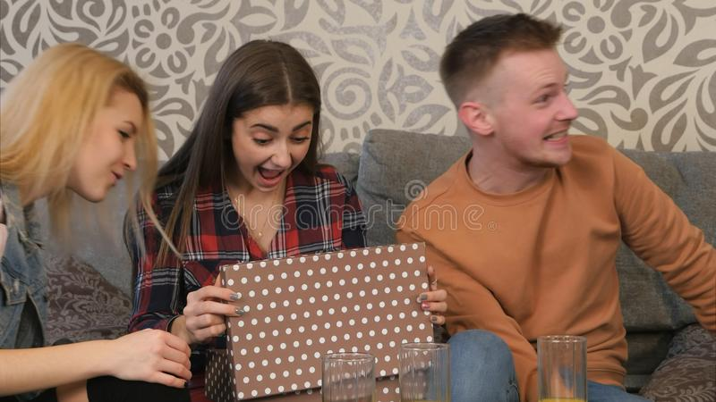 美丽的女孩打开礼物盒并且对什么惊奇和满意她看见 免版税库存照片