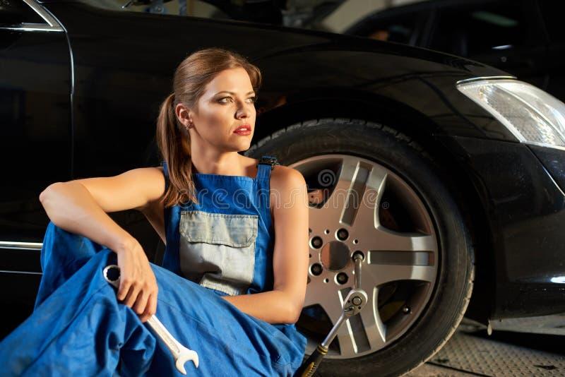 美丽的女孩技工在黑汽车附近轮子坐 图库摄影