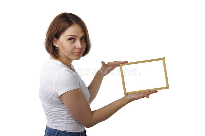 美丽的女孩拿着一个轻的木制框架 图库摄影