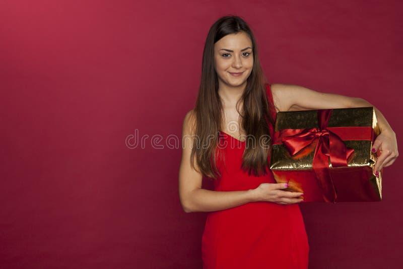 美丽的女孩拿着一件恰好被包裹的礼物 库存照片