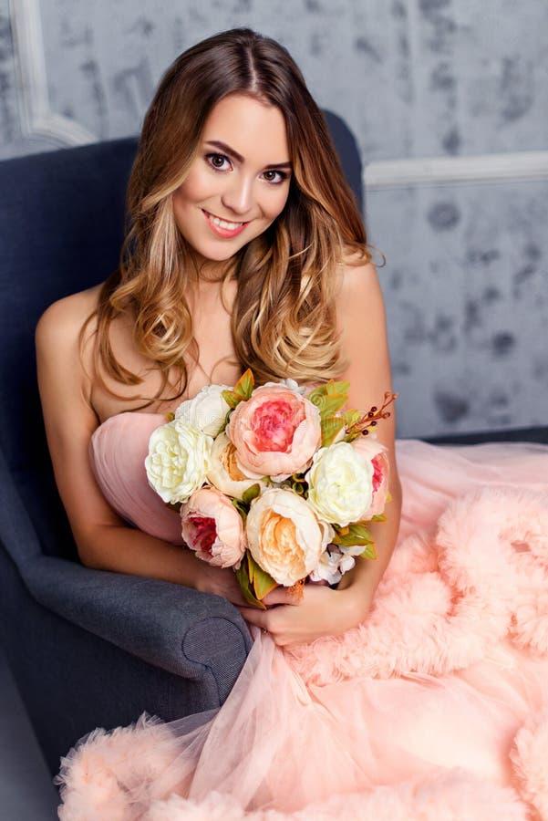 美丽的女孩拿着花花束和坐在内部的椅子 库存图片
