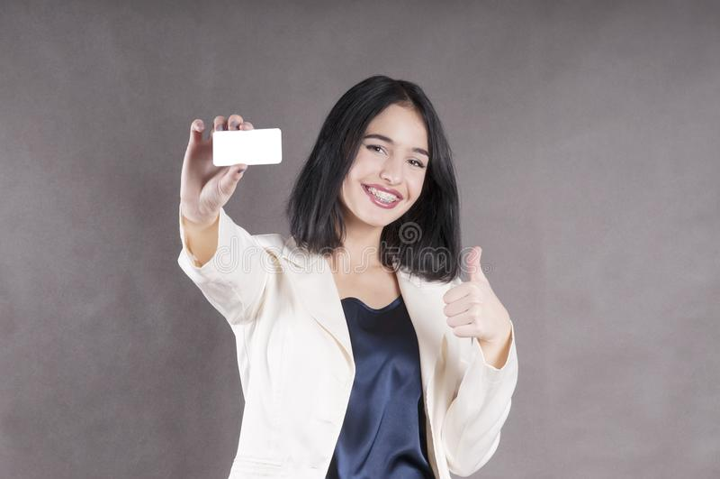 美丽的女孩提供名片演播室营销括号 免版税库存照片