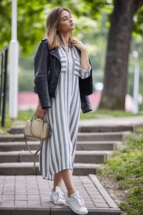 年轻美丽的女孩时髦的streetwear黑色皮夹克长的镶边白色服装运动鞋的和有一时兴的袋子strol的 库存图片
