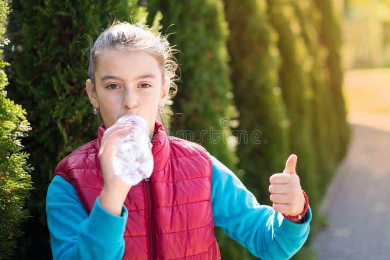 美丽的女孩是饮用水热的太阳在公园 免版税图库摄影
