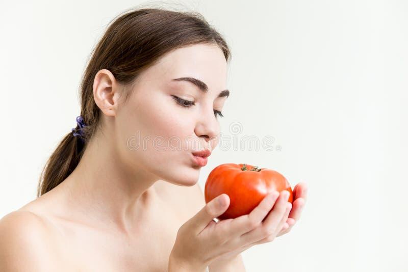 美丽的女孩显示并且亲吻一个大红色蕃茄健康高营养菜 免版税图库摄影