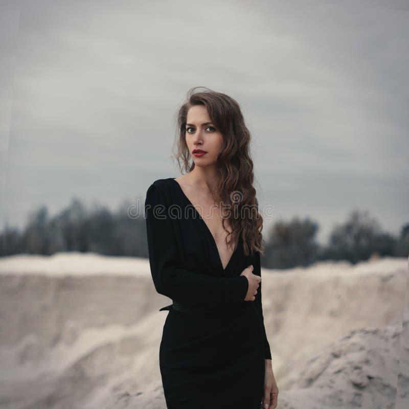 美丽的女孩有摆在沙子的卷发的黑葡萄酒礼服的 减速火箭的dres的妇女 担心的肉欲的情感 减速火箭 免版税库存图片