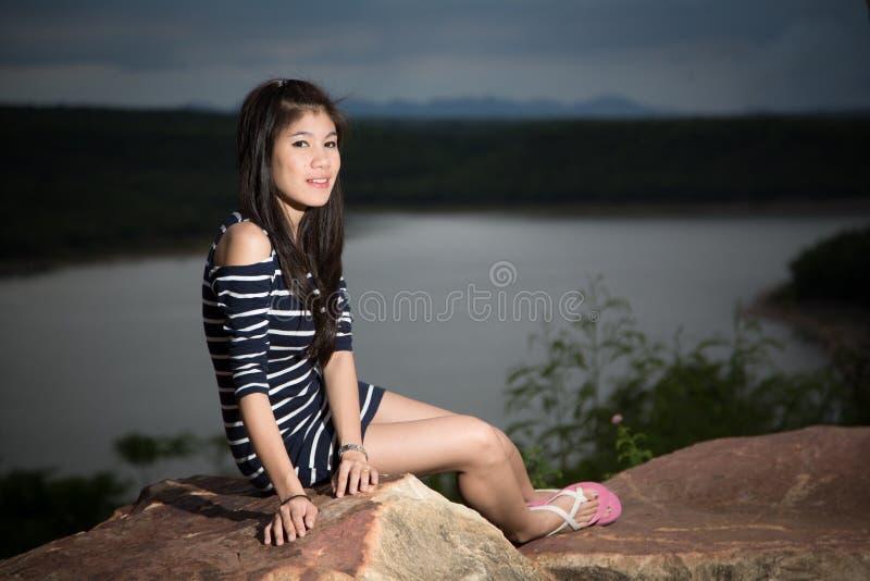 美丽的女孩有河和天空背景 免版税图库摄影