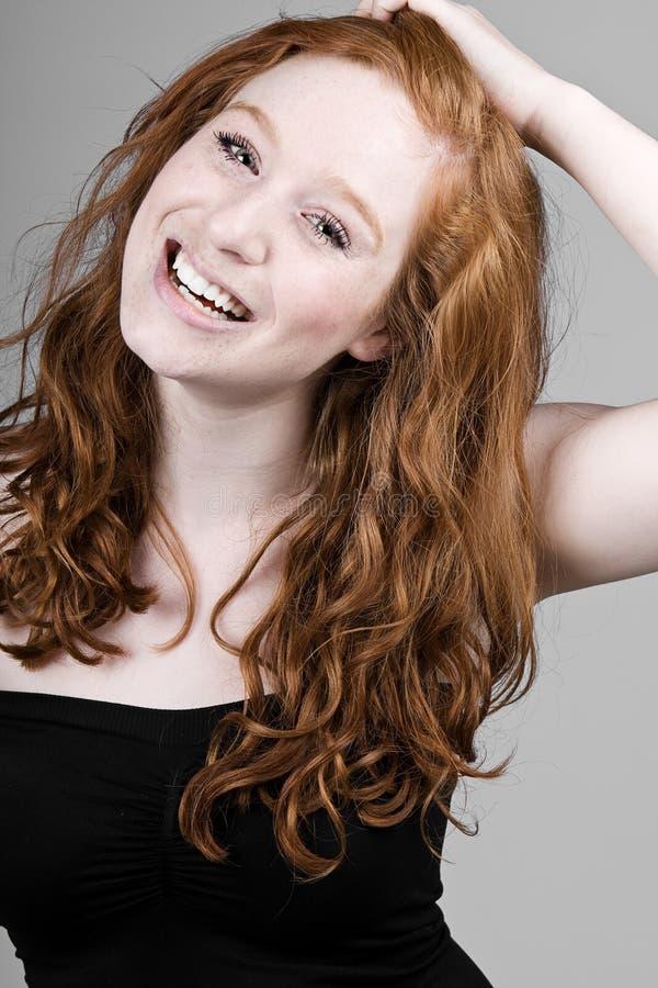 美丽的女孩朝向红色微笑 免版税库存照片
