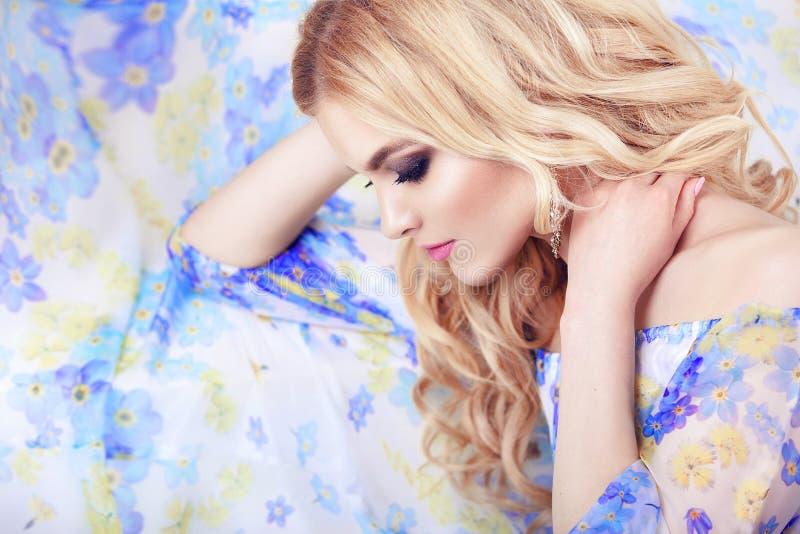 美丽的女孩模型妇女画象专业makiyad和头发在花在花卉背景,明亮的口气,桃红色锂穿戴 库存图片