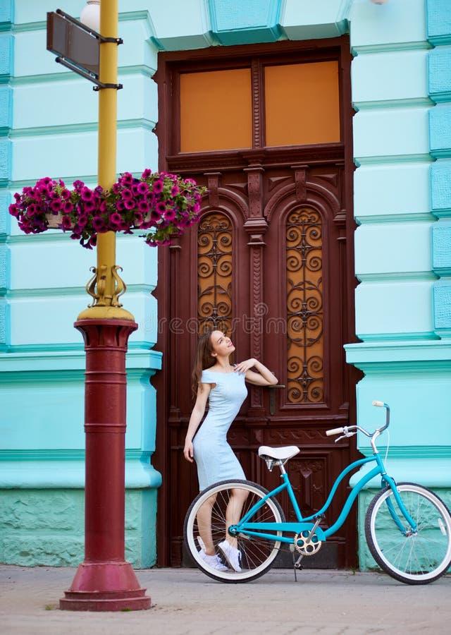 美丽的女孩浪漫画象在葡萄酒门,减速火箭的自行车附近的 库存照片