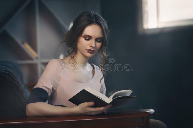 美丽的女孩热心地读书开会 免版税库存图片