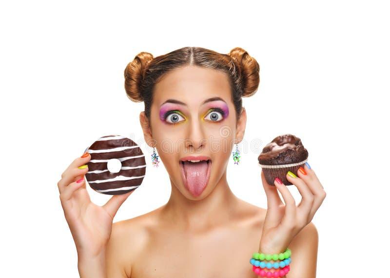 美丽的女孩用五颜六色的多福饼和松饼 免版税库存图片