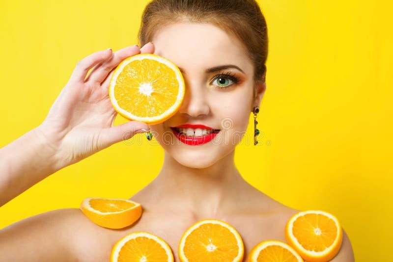 美丽的女孩用桔子和构成 免版税库存照片