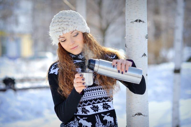 美丽的女孩用热水瓶和杯子热的茶在冷淡的冬日 免版税库存图片