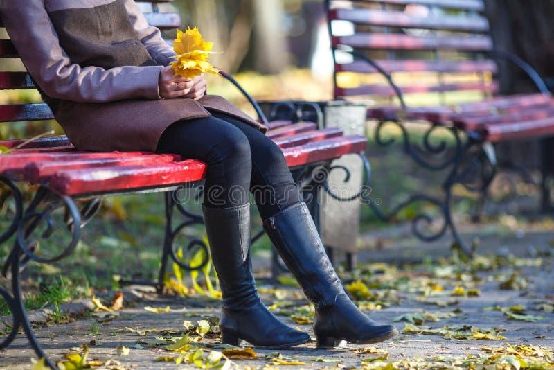 美丽的女孩画象坐长凳在公园并且放松, ye 图库摄影