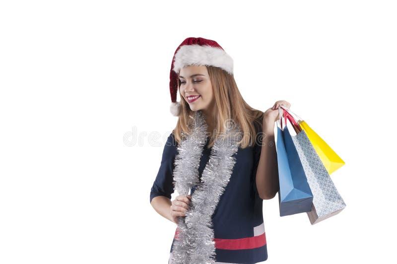 美丽的女孩白肤金发的盖帽圣诞老人,被隔绝的购物袋 免版税库存照片