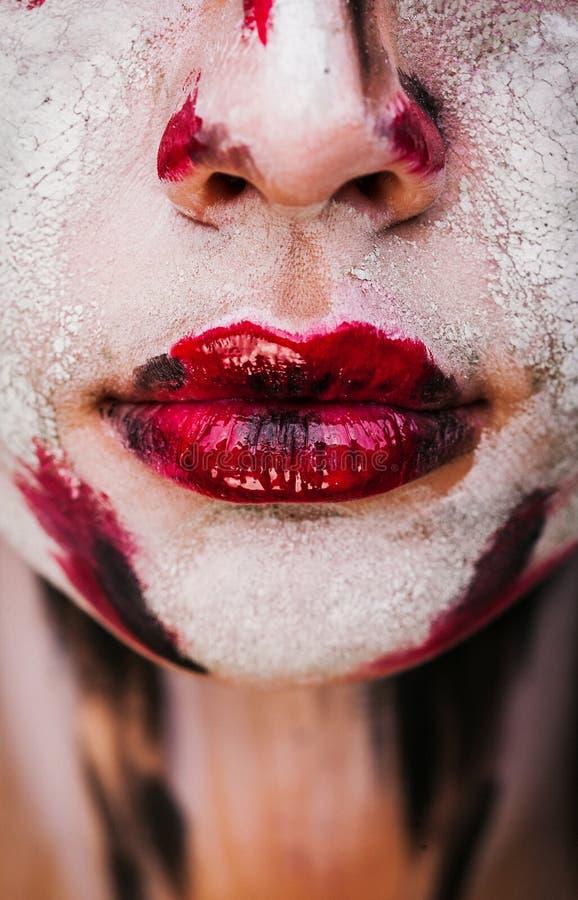 美丽的女孩的嘴唇有油漆的在他的面孔 图库摄影