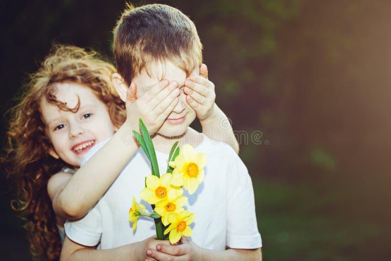 美丽的女孩盖她的男朋友的眼睛的和男孩用bouque 库存照片