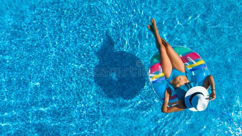 美丽的女孩空中顶视图从上面游泳池的,放松在可膨胀的圆环多福饼的游泳在家庭的水中 免版税图库摄影