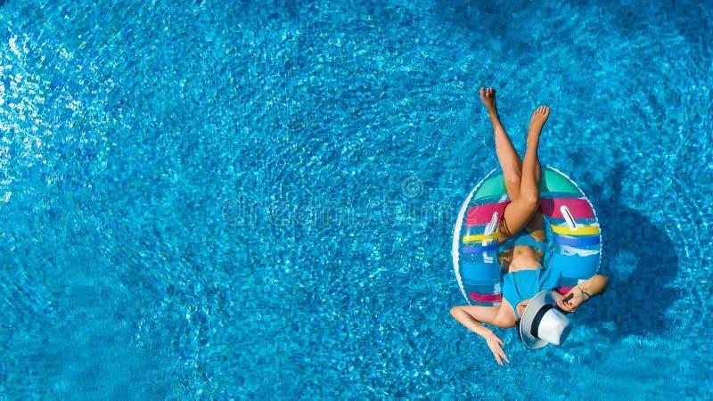 美丽的女孩空中顶视图从上面游泳池的,放松在可膨胀的圆环多福饼的游泳在家庭的水中 免版税库存照片