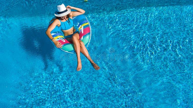 美丽的女孩空中顶视图从上面游泳池的,放松在可膨胀的圆环多福饼的游泳并且获得乐趣在水中 免版税库存图片