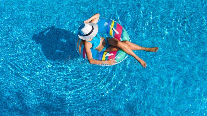 美丽的女孩空中顶视图从上面游泳池的,放松在可膨胀的圆环多福饼的游泳并且获得乐趣在水中 库存图片