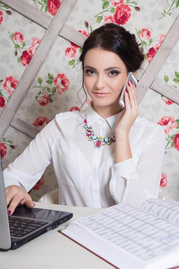 美丽的女孩经理在有笔记本和电话的秀丽演播室在手中 库存照片