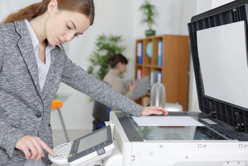美丽的女孩运行的影印机在现代办公室 库存图片