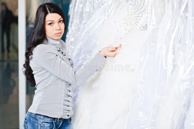美丽的女孩选择她的婚礼礼服 画象在新娘sa中 免版税图库摄影