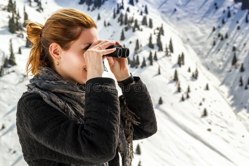 美丽的女孩通过在积雪覆盖的山背景的双筒望远镜看  免版税库存照片