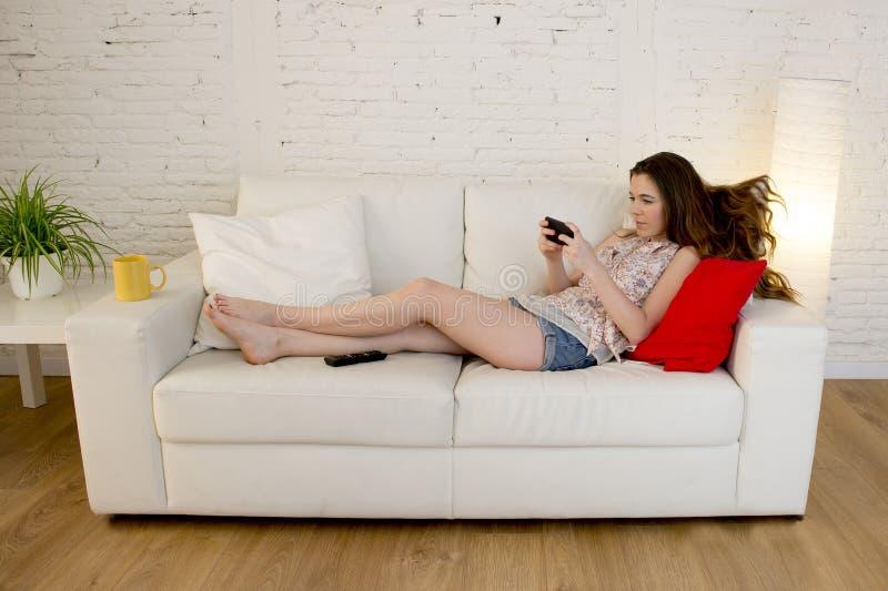 年轻美丽的女孩长沙发在家放松了使用手机微笑愉快和快乐 图库摄影