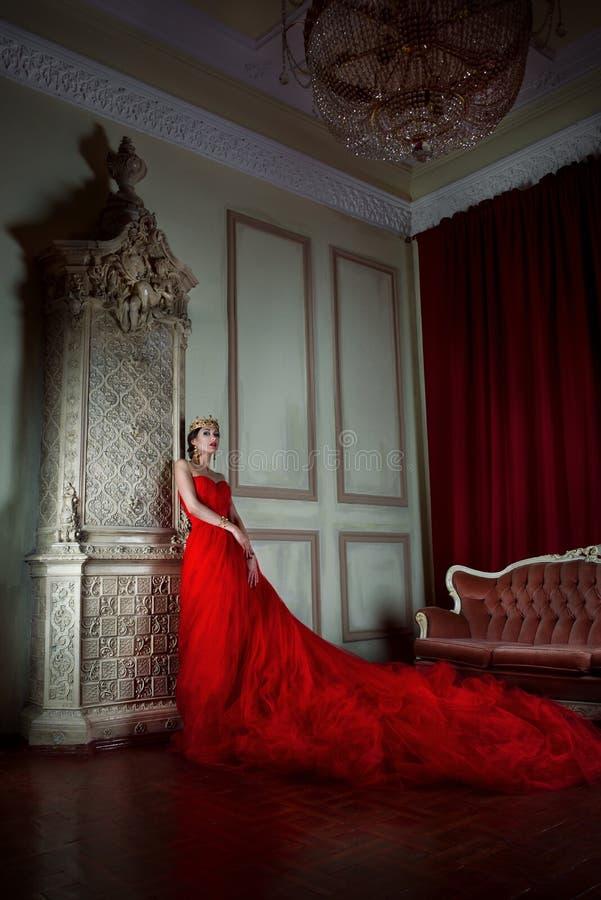 美丽的女孩长的红色礼服的和皇家冠的 免版税库存照片