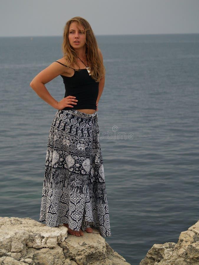美丽的女孩长的裙子石头 免版税库存图片