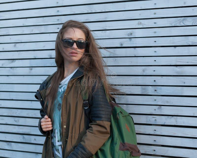 美丽的女孩长的头发 旅游夹克,背包 墙壁空白木 库存照片