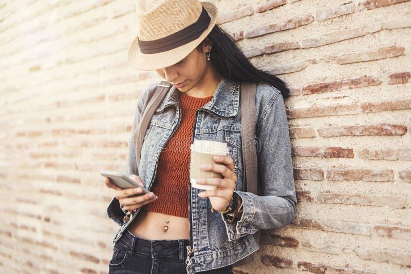 美丽的女孩饮用的咖啡和看她的电话 免版税库存照片