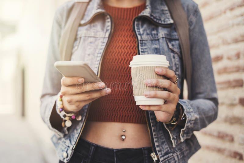 美丽的女孩饮用的咖啡和看她的电话 免版税图库摄影